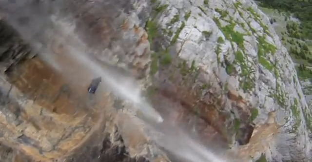 Wingsuit stuntman over waterfall