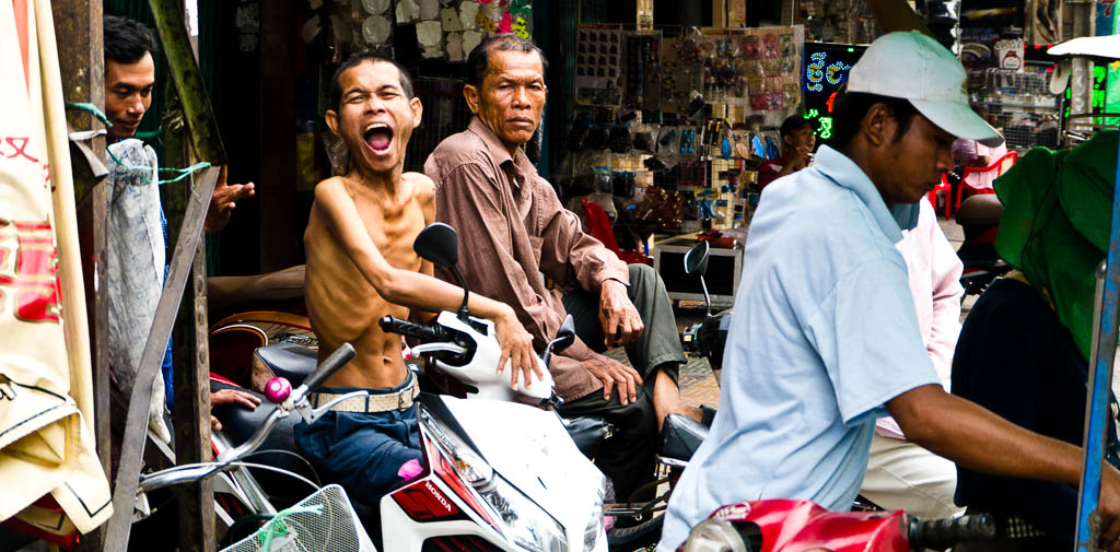 Street Photography in Phnom Penh, Cambodia by Tim Kelsall - moto driver shows his feelings for being photographed