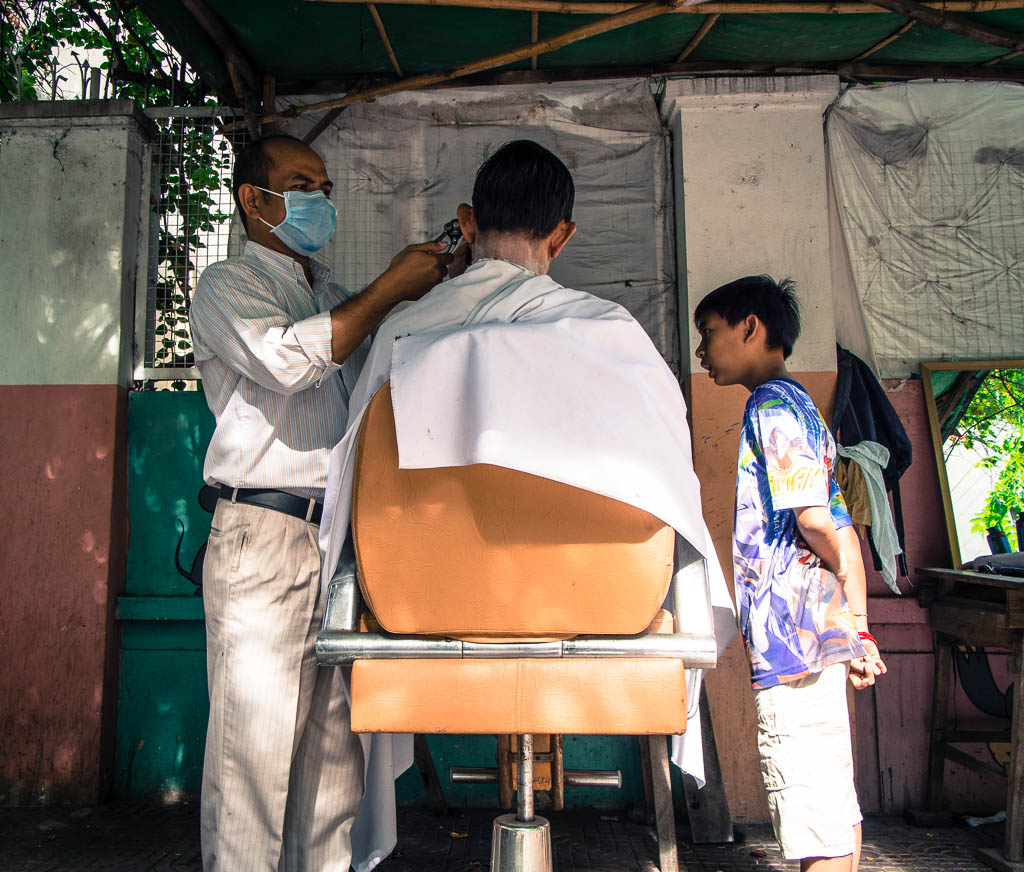Street Photography in Phnom Penh, Cambodia by Tim Kelsall - open air barber shop at Street 51